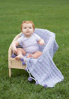Pom-poms and ripples come together to create this cute and cozy crocheted baby blanket. Shown in Patons Beehive Baby Sport.