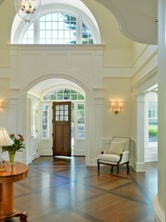 FOYER – great example of an impressive way to welcome guests. Love the molding! Bright entry and great use of windows and inlaid wood flooring.