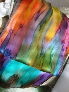 This gorgeous multi colored streaked scarf is hand painted and is 100% silk. Hand hemmed as well. Lovely mixture of many colors dripping into each other to create a lovely picture for you to wear with your favorite outfit. Imagine this with a Winter White outfit!! I challenge you to find an outfit it wont look great with!! This scarf is 11 x 58-60 (27.940 cm x 147.32cm-152.40 cm) and should be dry cleaned or hand washed in cold water. Low iron steam.