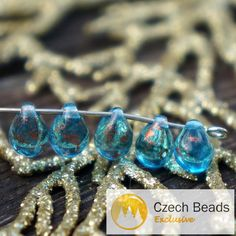 Color: Clear Turquoise / Gold Spotted Size (mm): 7mm x 5mm Shape: Teardrop / Tear Drop / Drop Sold in packs of 50 pcs