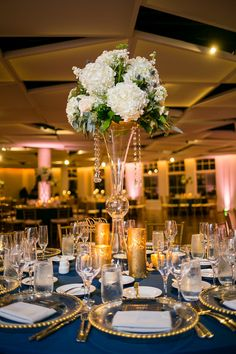We added gold uplighting to this reception and pinspotting to the white centerpieces for a more formal and modern vibe. See this real wedding and more by following our boards!