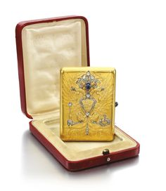 An Imperial Presentation Fabergé jewelled gold cigarette case, Moscow, 1915 the lid repoussé and chased with the Imperial eagle, set with rose- and circular-cut diamonds and a cabochon sapphire highlighting the crowns, beaks, shield, orb, sceptre, talons and tail feathers, above the dates 1613 and 1913 in highly stylised Slavonic script, sapphire thumbpiece, struck KF in Cyrillic and K. Fabergé in Cyrillic beneath the Imperial Warrant