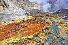 Photo of the sulphur deposits, volcanic rocks and streams that blanket the volcano landscape of White Island in New Zealand.