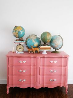Arrangement of collection of globes on a painted dresser.