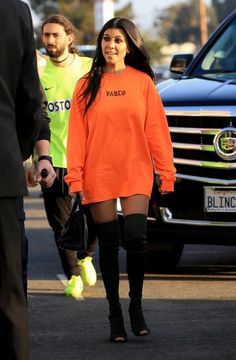 Reality star Kourtney Kardashian is spotted at Kanye West's 'Famous' visual premiere at the LA Forum in Los Angeles, California on June 24, 2016. Kourtney was wearing an orange 'Pablo' shirt as a dress with black thigh high boots.