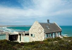 Stone Beach Cottage | Set on a private nature reserve overlooking several miles of undisturbed beach in Paternoster, on the West Coast of South Africa, the cottage is Built from Local Stone and designed to blend in. What does pop out are the pale Aqua of the shutters and gates, a color inspired by the sea. You find subtle touches of it throughout the house.