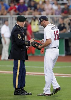 FORT BRAGG, NC - JULY 03: Sgt. 1st Class Corey M. Calkins is greeted after throwiing the ceremonial first pitch by Jeff Francoeur #18 of the Atlanta Braves prior to the game between the Miami Marlins and Atlanta Braves at Fort Bragg Field on July 3, 2016 in Fort Bragg, North Carolina. The Fort Bragg Game marks the first regular season MLB game ever to be played on an active military base. (Photo by Streeter Lecka/Getty Images)