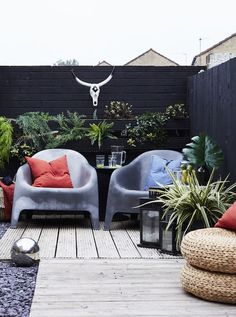 En utendørs terrasse med grå stoler og planter.