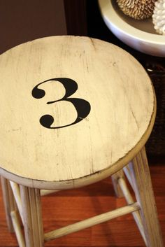 If you are a regular reader, you know I just painted this stool, just a few days ago, Friday to be exact. The Stool and the Pigeon Part I. Painted Chairs, Painted Furniture, Furniture Ideas, Stencil, Burlap Garland, Wooden Stools, Letters And Numbers, Bar Stools, Repurposed