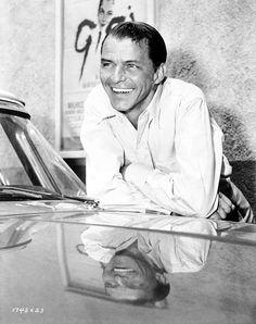 Medium BTS shot of Frank Sinatra as Capt. Tom Reynolds leaning on car.