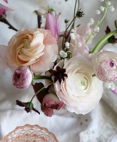 blushing magnolia, japanese ranunculus, chocolate cosmos, and lily of the valley in depression glass