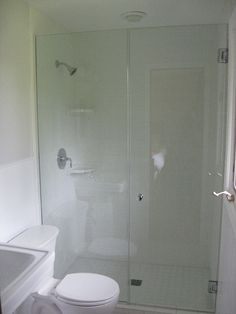 Small master bath with frameless shower door and white subway tile