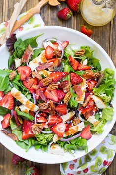 Strawberry Fields Salad with bacon, feta cheese, glazed pecans, grilled chicken. and a sweet and tangy dressing.