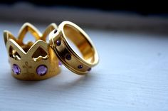 king and queen rings, such a cute idea. dont like the purple and gold but silver with diamonds would look great.