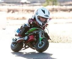 Young kid riding a motorcyle with helmet on