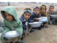 Afghan children line up for food distributed by UNICEF at Maslakh refugee camp, approximately 6 miles west of Herat in western Afghanistan. (Behrouz Mehri/AFP/Getty Images)