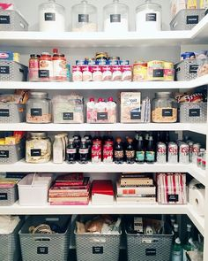 Lovely walk in pantry features  a top row filled with labeled canisters filled with baking products and the second and third rows filled with round acrylic trays housing tomato sauces and soup cans as well as acrylic bins filled with seasonings in envelopes.