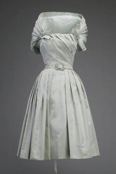"Cocktail Dress, Christian Dior, Paris, France: ca.1955, silk taffeta. ""The expertly draped bodice and attached shawl of this Christian Dior ready-to-wear cocktail dress are complex construction details usually found only in couture collections. These elements require a great deal of skilled labor usually considered too expensive for the ready-to-wear market."""