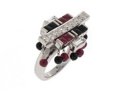 Cartier Baiser du Dragon Ruby and Diamond Ring = Crafted in pallid white gold, this pagoda style ring recreates the oriental-inspired designs in rich red and inky black of the jewelry house's brilliant Art Deco past. A central row of diamonds is accented by sleek sections of bufftop onyx and ruby, while a delicate fringe of onyx and ruby dangles completes the look. Circa 2003