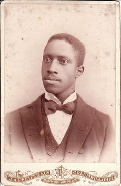 A well dressed African American man poses for his portrait at the J. A. Pfeifer & Company gallery in Columbus, Ohio