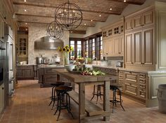 A French country kitchen with an imposing stone enclosure around the stove. The cabinets are painted in muted shades of beige and brown. An adjacent plank table with four stools acts as both a breakfast area and an additional preparation area, if needed. True to French country design, this kitchen accents the natural materials with sunflowers in a glass vase on the table and smaller yellow bouquets in front of the windows above the sink.