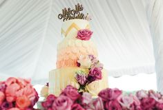 Stunning white, pink, and gold wedding cake with purple and pink flowers and gold topper. See more from this peach outdoor wedding in Blountville at @chateauselah! Rentals by Celebrate Rentals, images by Elizabeth Large | The Pink Bride® www.thepinkbride.com