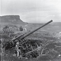 Unpublished. A crew maneuvers an enormous piece of artillery during the Battle of Saipan, 1944. In the waning days of the struggle for the island, thousands of Japanese civilians and troops committed suicide, rather than surrender to American troops. Many leapt to their death from the top of sheer cliffs that fall 200 feet to rocks and surf below.