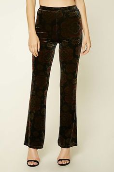 A pair of velvet pants featuring an ornate abstract print, a mid-rise, straight leg, and an elasticized waist.