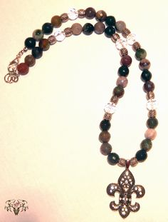 This is a all natural stone with crystals and silver spacers along with a rhinestone fleur de lis pendent. Come visit us at www.twistedthingamajigs.com to get all natural stone jewelry cheaper than wholesale prices!