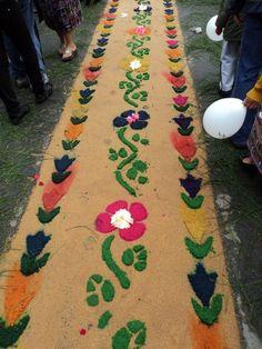 Alfombras de aserrín de colores, flores y adornos para el paso de la Procesión de Corpus Christi en Patzún