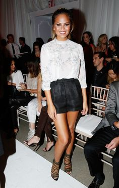 Chrissy Teigen wears a lace trim floral blouse, high-waisted shorts, and strappy heels