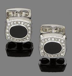 A pair of onyx and diamond cufflinks  Each oval onyx plaque within a single-cut diamond surround, to t-bar connectors, diamonds approx. 0.75ct total, plaque length 1.7cm