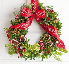 Give a standard evergreen wreath a sweet touch. Start with a boxwood wreath, purchased or made by inserting boxwood sprigs into a damp floral foam wreath base. Add hypericum berries and hydrangea blooms from a flower shop and candy and berries from a crafts store. Hang the wreath with the ribbon used to form a bow.