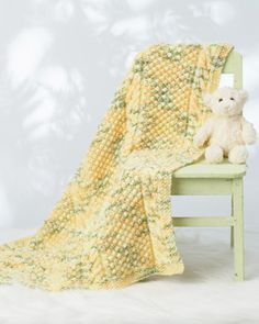 Brighten up baby's nursery with this sweet blanket featuring classic cable details. Shown in Bernat Li'l Tots. #knit #baby