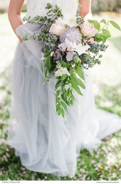 Two piece wedding dress with lace detailed top and pastel blue long skirt and peach rose bouquet   Photographers: Inge Kooiman Fotografie   Planning & concept: Elsa Schaddelee   Wedding dress: Wild at Heart Bridal   Flowers: Mullers Floral Art   Hair & Make Up: The Beautiful Bride Company   Headpiece: Naturae Design