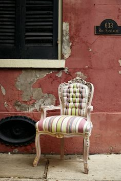 An eye-catching chair reupholstered in Gigi from the Annie Sloan Fabric Collection set against a lovely backdrop of one of New Orleans' many colorful buildings.