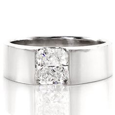 Solstice - Solstice is a delightful low-profile solitaire engagement ring. The diamond set within the wide band is suspended in a half-bezel along the length of the stone. Brilliance from the 1.0 carat radiant cut is enhanced by the smooth polished edges of the band.