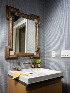 Blue-and-Brown Powder Room Stormy-blue rectangular mosaic tiles line the walls of this eclectic powder room that combines old and new motifs. A Celtic- inspired mirror with a distressed metallic frame contrasts beautifully with the contemporary maple vanity below. Layers of neutrals -- a white sink, dark brown honed granite countertop, and blond wood -- add to the sophistication of this room. A sleek wall-mount faucet with cross-bar handles adds the final touch.