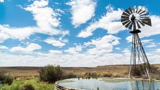 A linear midday timelapse of a windmill blowing in the wind next to and old zinc farm dam with scattered clouds against a bright blue sky in a typical Karoo landscape. Blowing Wind, Windmills, Geology, Stock Footage, Wind Turbine, South Africa, Clouds, Bright, Sky