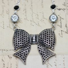 "Beautiful Bow Necklace. Vintage Style :)      LOVE LOVE LOVE this Vintage Inspired bow necklace. How amazing would this look with your spring dresses?     Antique silver bow focal is 2"" x 1.5"" and has embedded sparkling crystals. Two jet black and two crystal jewels dangle from a 16"" silver tone necklace."