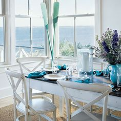This white dining room features white wooden chairs, turquoise accents, and a gorgeous view.