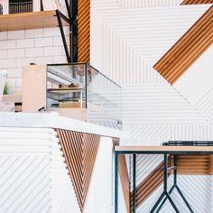 Juice Served Here, chaîne de jus de fruit à la mode, investit la célèbre West 3d Street à LA. On doit le design de cette nouvelle boutique au studio Bells & Whistles. Des installations en bois géométriques qui courent le long des murs, une palette de couleurs noir/blanc avec des touches jaune-orange, une esthétique scandinave qui fonctionne bien et qui crée un rendu sophistiqué. Les meubles ont été spécialement créés pour le lieu. Un magasin stylé et contemporain pour des jus sains et…