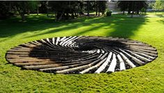 """The sculpture, """"Carbon Sink: What Goes Around Comes Around,"""" was installed by British artist Chris Drury. A spiral of logs made from trees killed by a pine-beetle infestation, the center of the 36-foot-diameter sculpture featured coal-blackened logs surrounded by lumps of coal."""