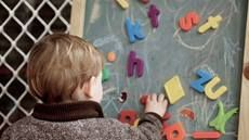 Close-up of preschool child playing with magnetic letters on a chalkboard