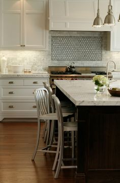 transitional kitchen design with creamy white kitchen cabinets, white carrara marble subway tiles backsplash, chrome yoke island pendants, espresso stained wood kitchen island, marble counter tops, and Emeco navy barstools.