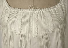 Detail of ca.1862 chemise (per Met Museum) with applied lozenges of embroidered edging between pintucks, and drawstring at neckline.