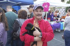 This man is holding one of the Labrador mix puppies that were looking for a home, and this little guy found it!