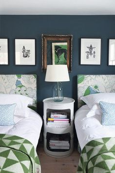 Sweet blue and green guest bedroom featuring dark blue walls and lots of pattern from headboard to quilt.