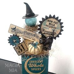 My Halloween Creation:  Vintage elements include cardboard Crescent Spice box, Moon Drug Co. label, milk bottle cap, black cat cupcake topper, mercury glass ball, silver lametta tinsel, silver mercury beads, Bingo marker, & Bingo square 31 and 13. Handmade witch hat and pumpkin with Paperclay + black Desden trim, turquoise & silver glass glitter, and cream sisal filler.