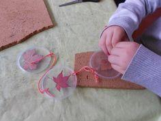 Mit gepressten Blättern beklebt und in Reihe aufgefädelt ergeben die Deckel der Eimerchen eine nette Fensterkette. Das schaffen auch Kinderhände ganz schnell.